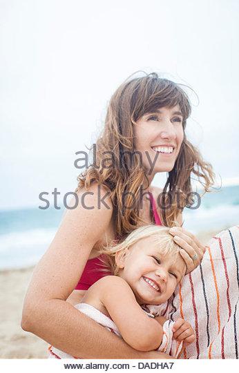 Mutter und Tochter am Strand lachen Stockbild