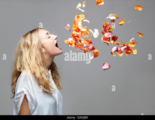 Junge Frau mit Mund öffnen eine Blütenblätter schweben in der Luft Stockbild