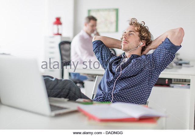 Junge Büroangestellte am Schreibtisch mit Hände hinter Kopf liegend Stockbild