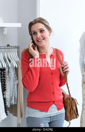 Junge Frau auf dem Handy im Modegeschäft Stockbild