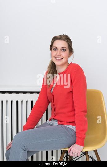 Porträt einer jungen Frau im roten Strickjacke Stockbild