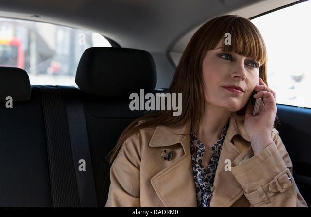Business-Frau mit Handy im Auto Stockbild