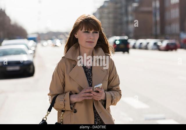 Frau mit Handy auf Straße Stockbild