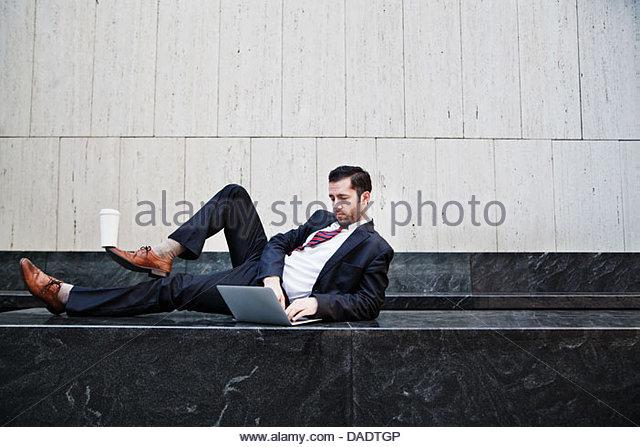Geschäftsmann auf Seite liegend, mit Laptop und Kaffee auf seinem Fuß balancieren Stockbild