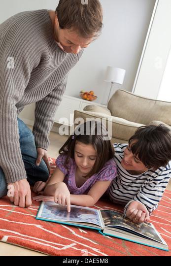 Tochter betrachten Bilderbuch mit Eltern Stockbild