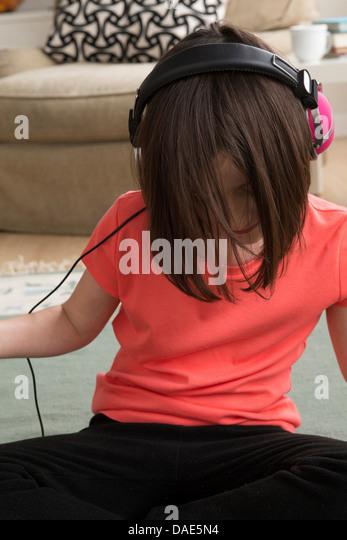 Mädchen mit Kopfhörern, Blick nach unten Stockbild