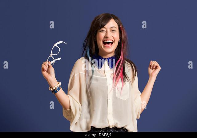 Porträt der jungen Frau mit gefärbten Haaren hält Gläser Stockbild