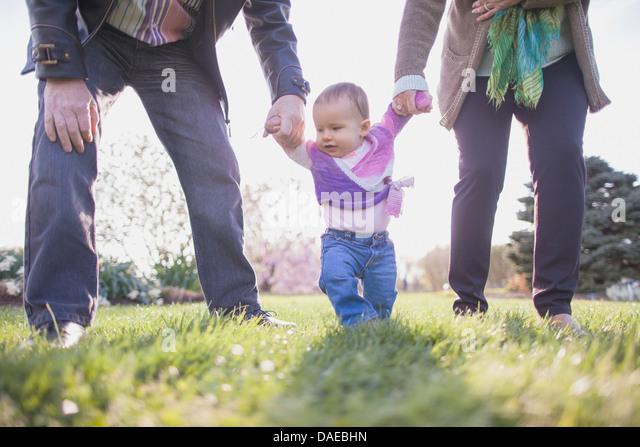 Großeltern, die Enkelin Händchen im park Stockbild