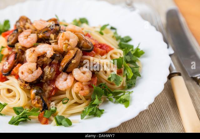 Pasta mit Meeresfrüchten und Weißwein auf Servietten Stockbild