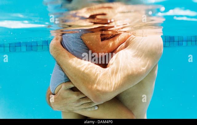 Vater Holding Tochter im Schwimmbad Stockbild