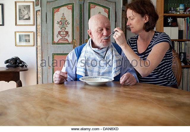 Enkelin zu ihrem Großvater Fütterung Stockbild