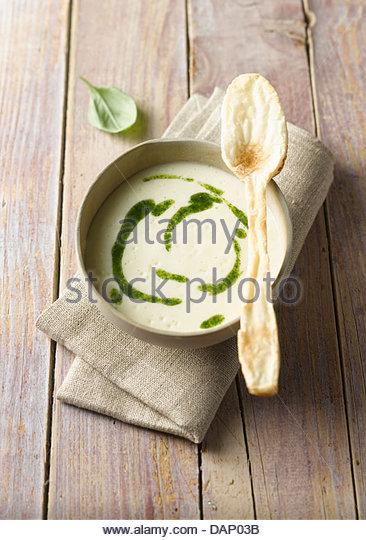 Schale der Kartoffel-Suppe mit Pesto und Blätterteig Löffel auf Holztisch, Nahaufnahme Stockbild