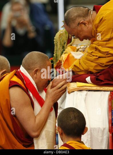 Ein Mönch kommt in Kontakt mit dem Dalai Lama (R) auf seinem Thron in Hamburg, Deutschland, 27. Juli 2007. Stockbild