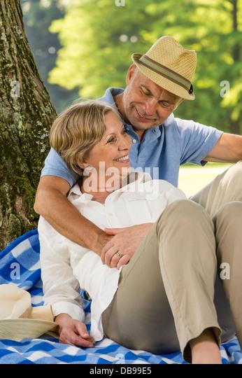Glückliche ältere Frau und Mann umarmt im park Stockbild