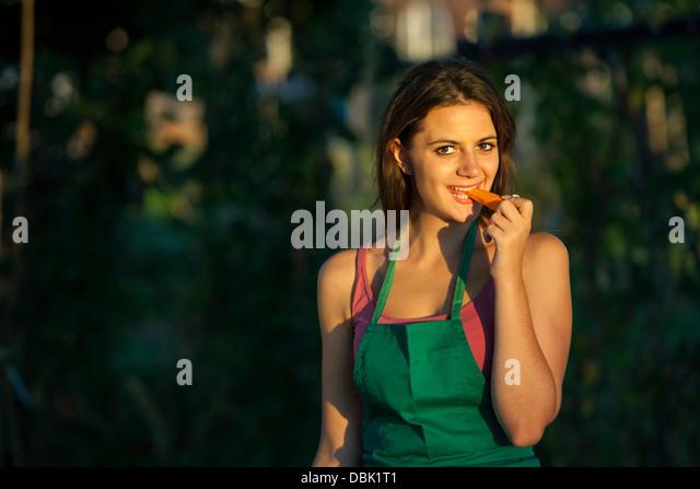 Junge Frau im Garten essen Karotten, Kroatien, Slawonien, Europa Stockbild