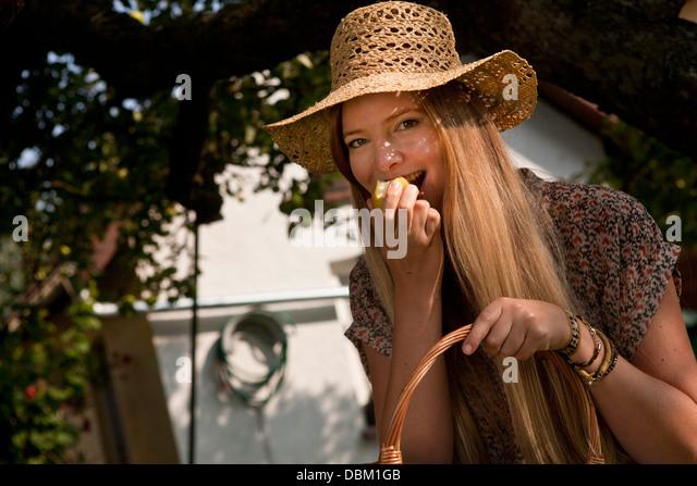 Einen Apfel essen Mitte Erwachsene Frau im Garten, München, Bayern, Deutschland Stockbild