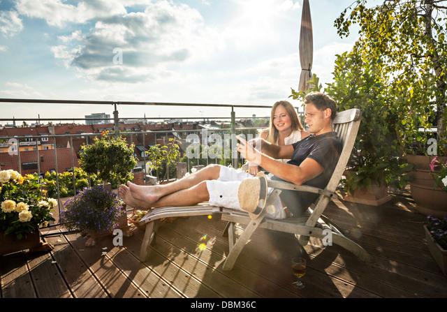Paar auf Balkon mit Handy, München, Bayern, Deutschland, Europa Stockbild