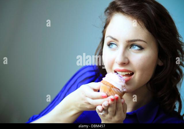 Frau mit braunen Haaren Essen einen Cupcake, Kopenhagen, Dänemark Stockbild