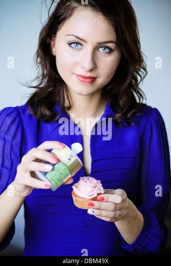 Frau im blauen Kleid Essen einen Cupcake, Kopenhagen, Dänemark Stockbild
