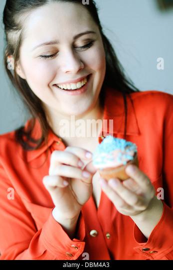 Frau im roten Kleid Essen einen Cupcake, Kopenhagen, Dänemark Stockbild