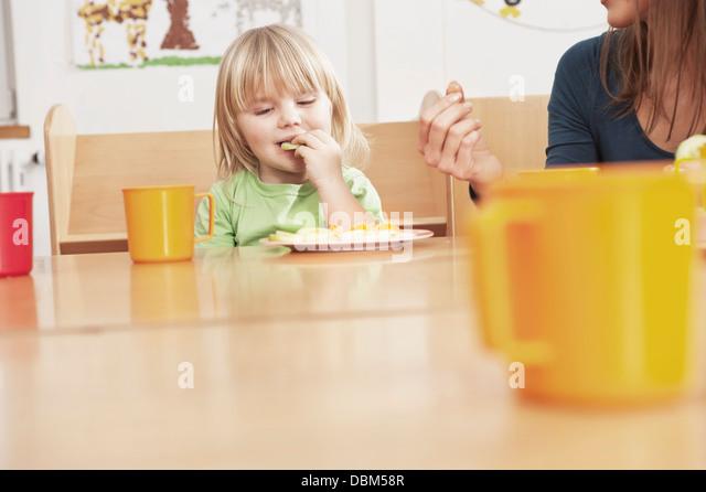 Mädchen und weibliche Pflegeperson Essen am Tisch, Kottgeisering, Bayern, Deutschland, Europa Stockbild