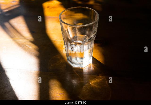 Wasserglas in der Nähe von leer Stockbild