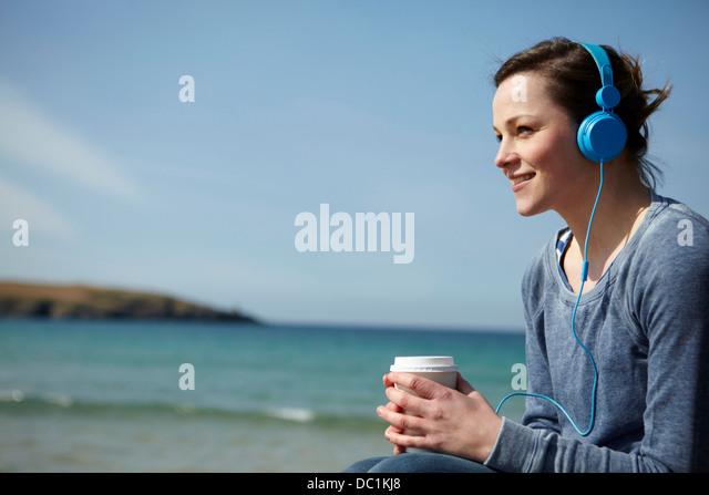 Junge Frau am Küste mit Kaffee und Kopfhörer Stockbild