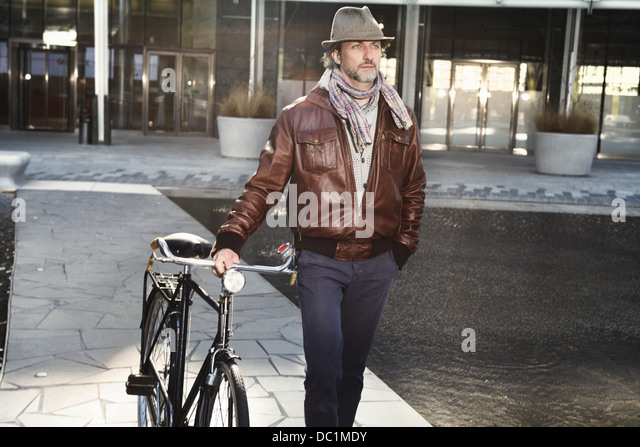 Mitte erwachsenen Mann zu Fuß mit dem Fahrrad in die Stadt Stockbild
