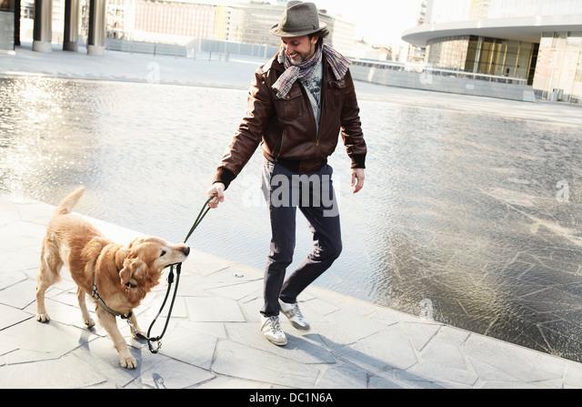 Mitte erwachsenen Mannes ziehen Leine am Hund in Stadt Stockbild