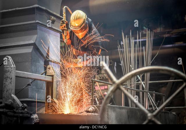Mann in Schutzkleidung bei der Arbeit in Stahlgießerei Stockbild