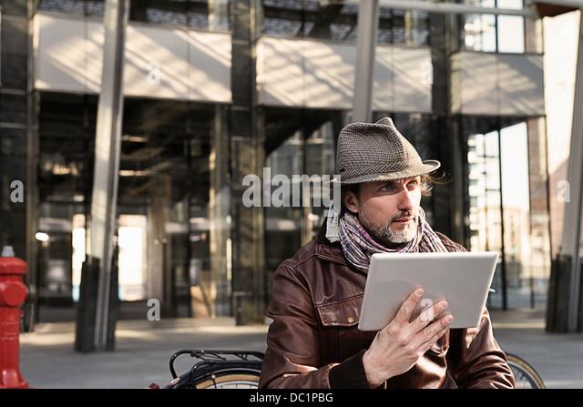 Mitte erwachsener Mann mit digital-Tablette und wegsehen Stockbild