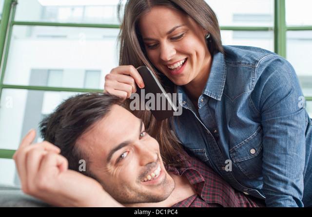 Nahaufnahme eines jungen Paares im Hause Flickschusterei mit Handy Stockbild