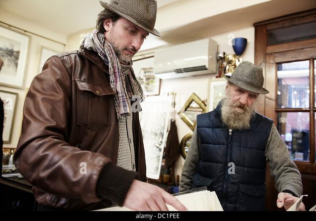 Senior und Mitte erwachsenen Mannes in Antiquitätengeschäft Stockbild