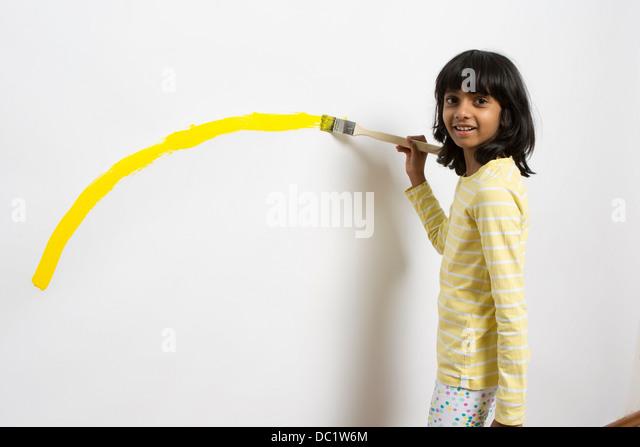 Porträt von Mädchen malen gelbe Kurve an Wand Stockbild