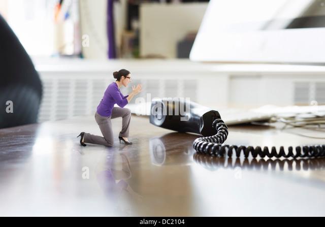 Geschäftsfrau, die durch große Telefonhörer auf übergroße Schreibtisch schreien Stockbild