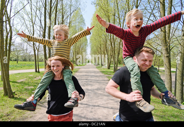Mutter und Vater racing mit zwei jungen auf Schultern durch den park Stockbild