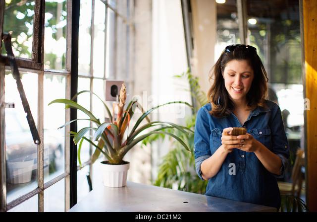 Mitte der erwachsenen Frau mit Handy drinnen Lächeln Stockbild