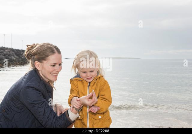 Mutter und Kleinkind an Küste erkunden Stockbild