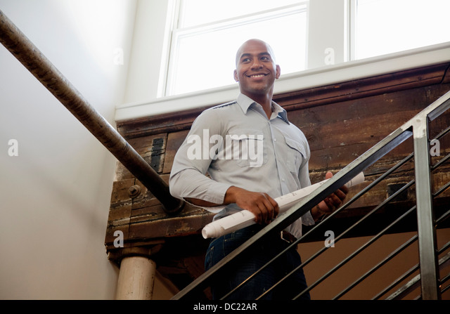 Mitte erwachsenen Mann, der aufgerollt Pläne auf Treppe Lächeln Stockbild