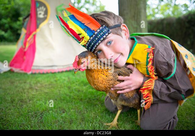 Junge Indianer Kostüm Holding Huhn gekleidet, portrait Stockbild
