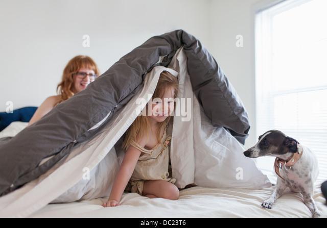 Mädchen, die versteckt unter der Bettdecke, Mutter und Hund auf Bett Stockbild
