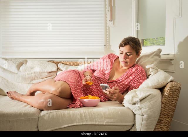 Frau liegt auf dem Sofa Schüssel Chips essen Stockbild