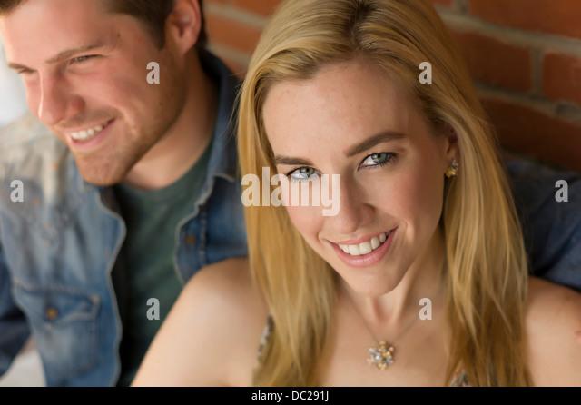 Porträt des Paares, lächelnde junge Frau im Mittelpunkt Stockbild