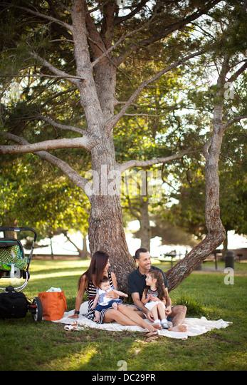 Familie mit zwei Kindern sitzen auf der Picknickdecke unter Baum Stockbild