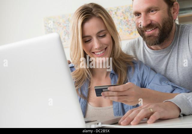 Mann mit Frau hält Kreditkarte Stockbild