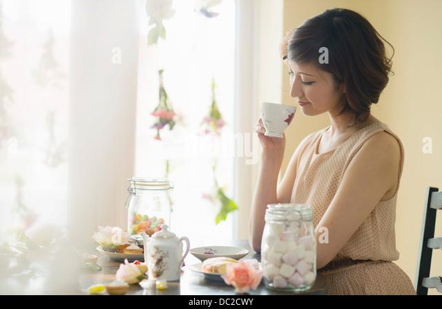 Frau blickte auf Teetasse Stockbild