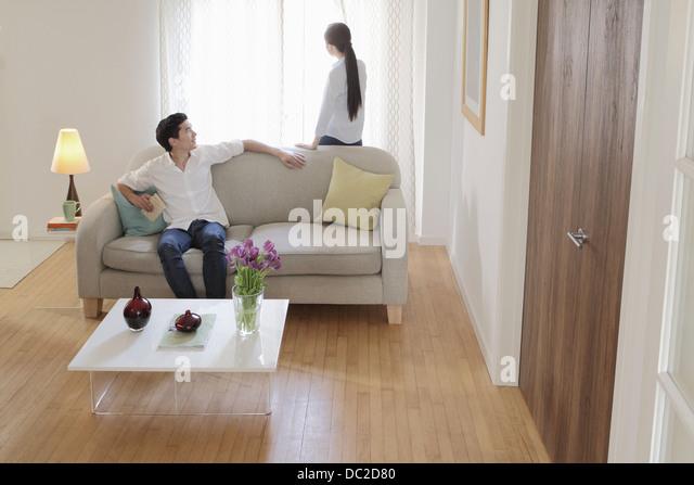 Mann sich wendend Runde auf Sofa Frau anschauen Stockbild
