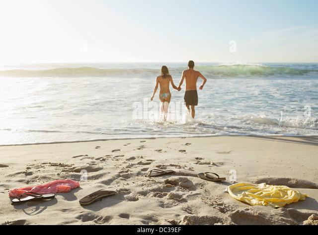 Paar Hand in Hand und waten im Ozean Stockbild