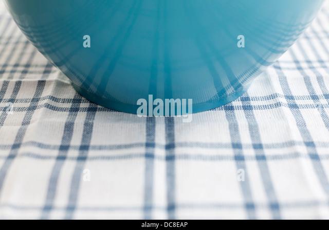 Nahaufnahme des blauen Plastikschüssel auf einer blau-weißen Tischdecke. Seitenansicht. Stockbild