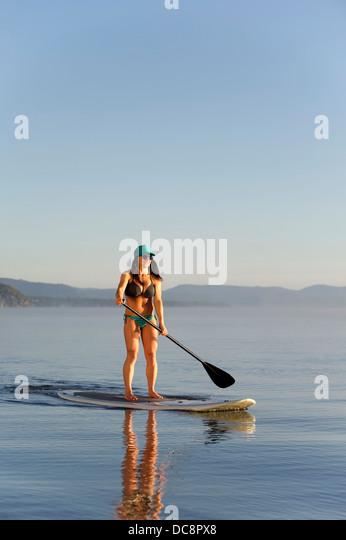 Eine Frau, Stand Up Paddling (SUP) am Lake Tahoe in den frühen Morgenstunden auf ruhigen spiegelglatten Wasser, Stockbild